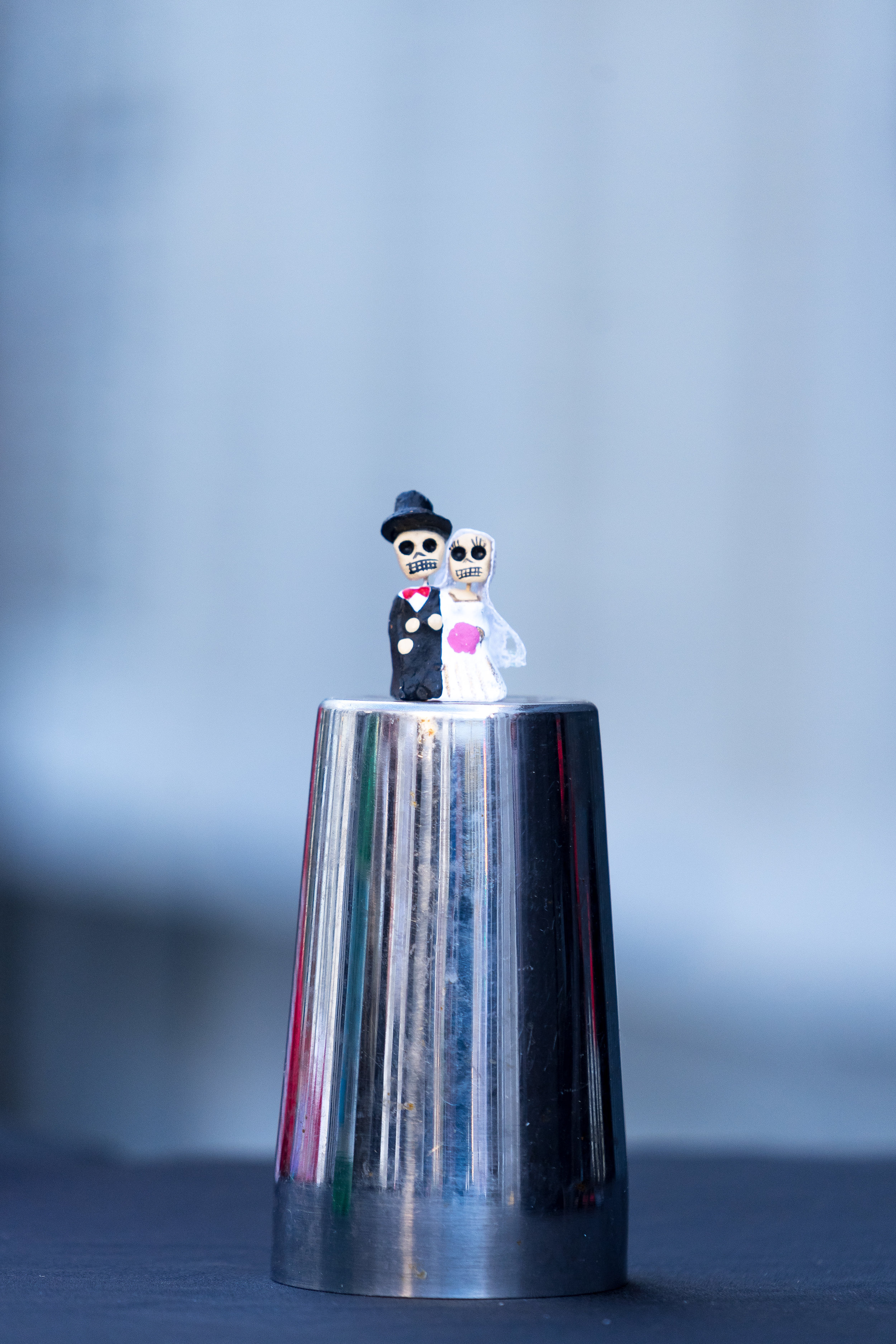wedding detail image of skull bride and groom on silver cup by destination wedding photographer adam cotton