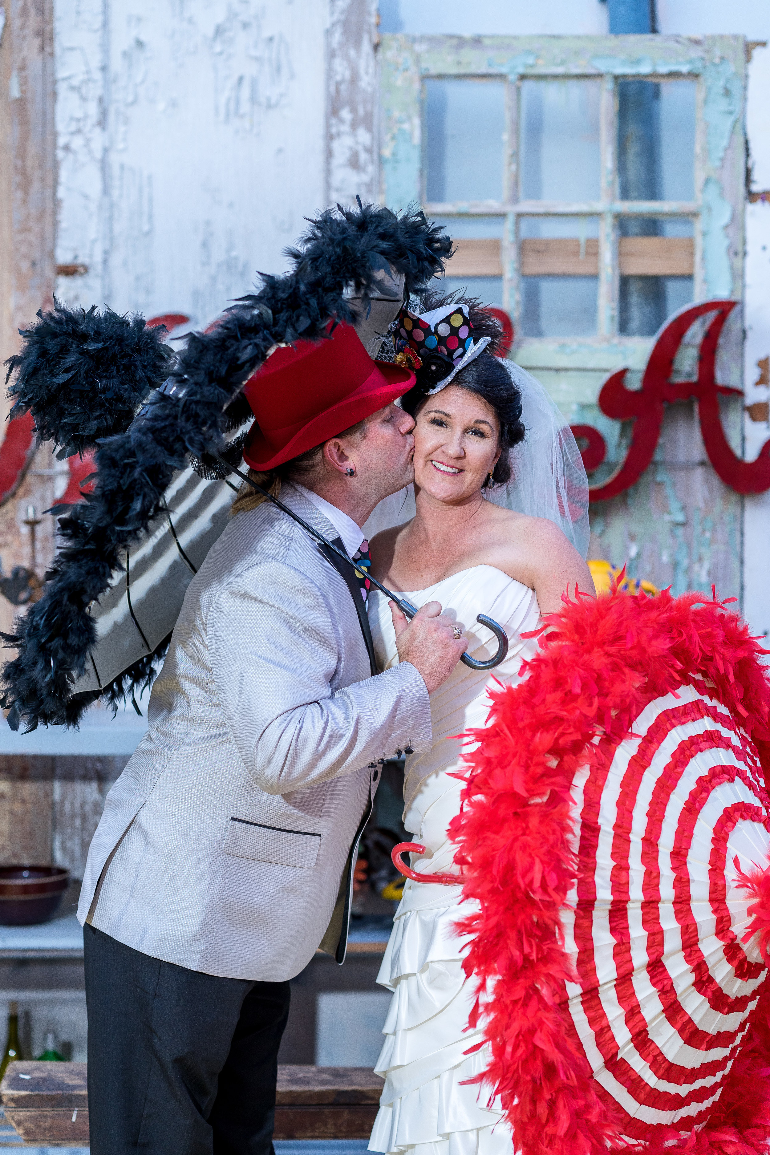 image of bride and groom with parasols kiss wedding with tux and dress