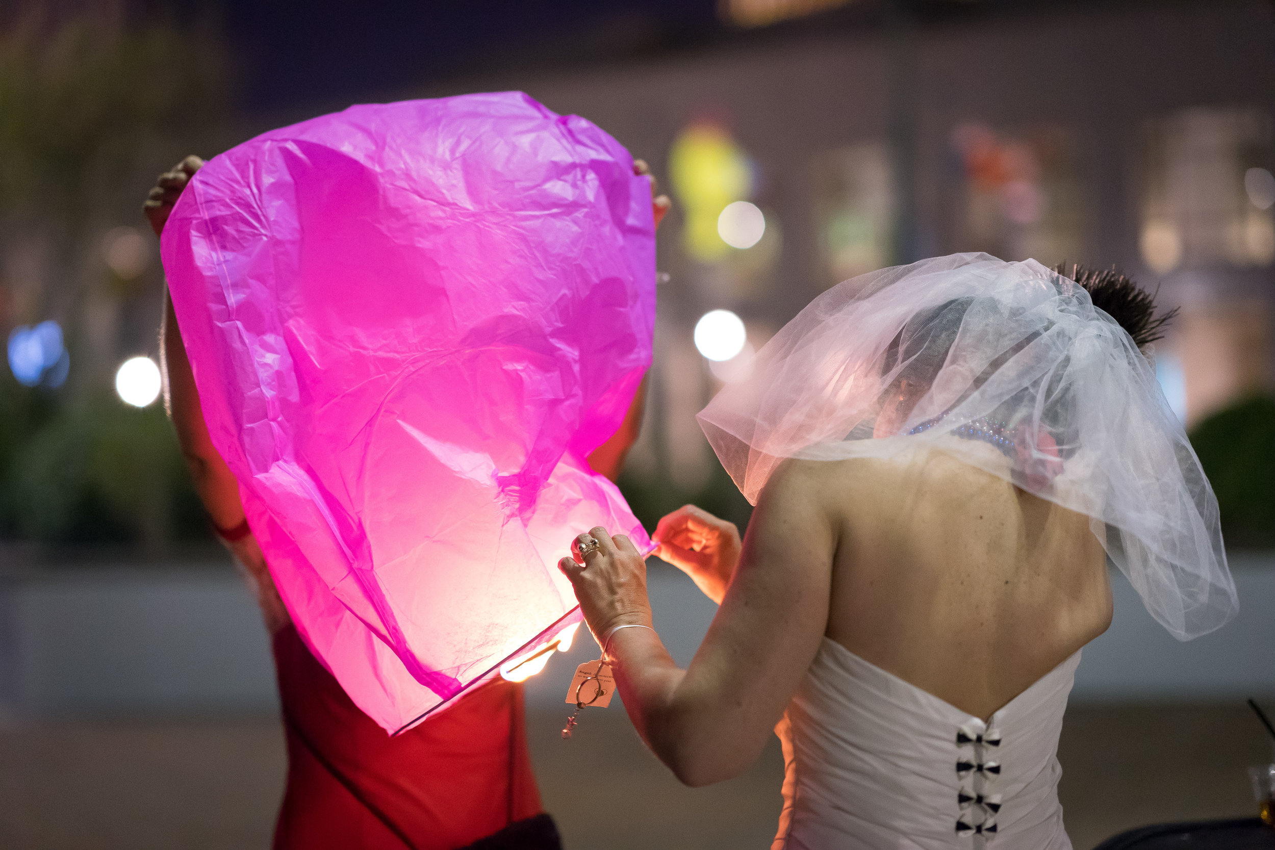 image of bride and mother lighting lantern after wedding reception