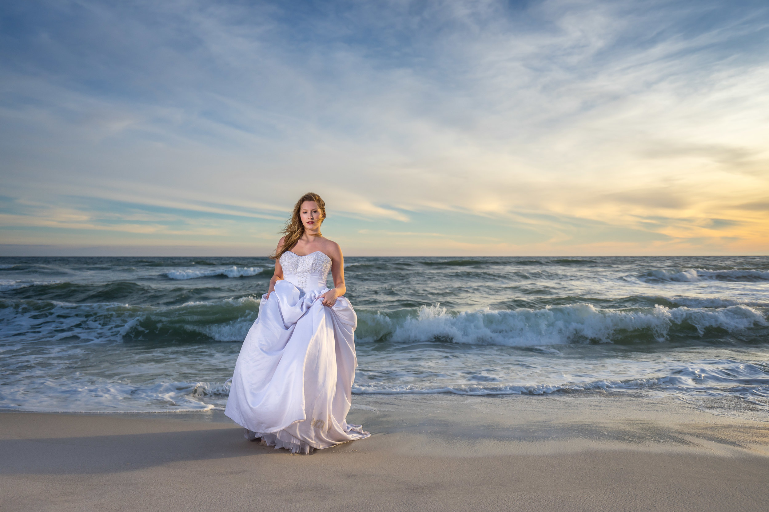 beautiful image of bride carrying soaked wedding dress on pensacola beach