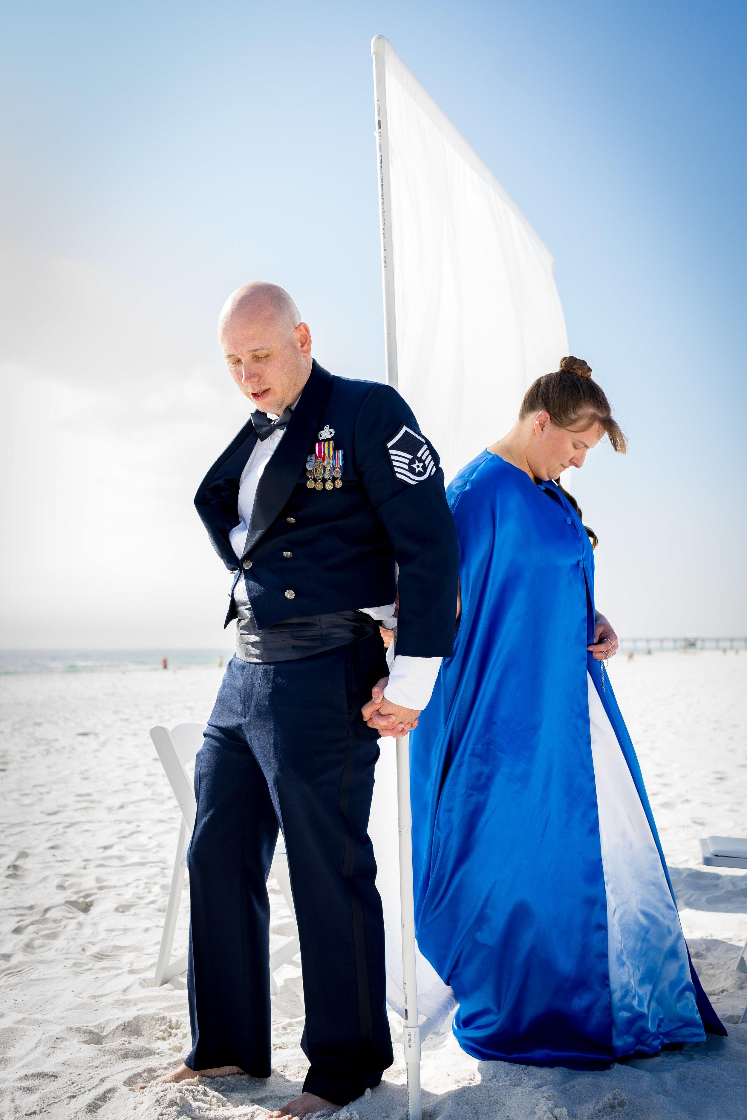 bride and groom praying pensacola beach wedding photographer adam cotton