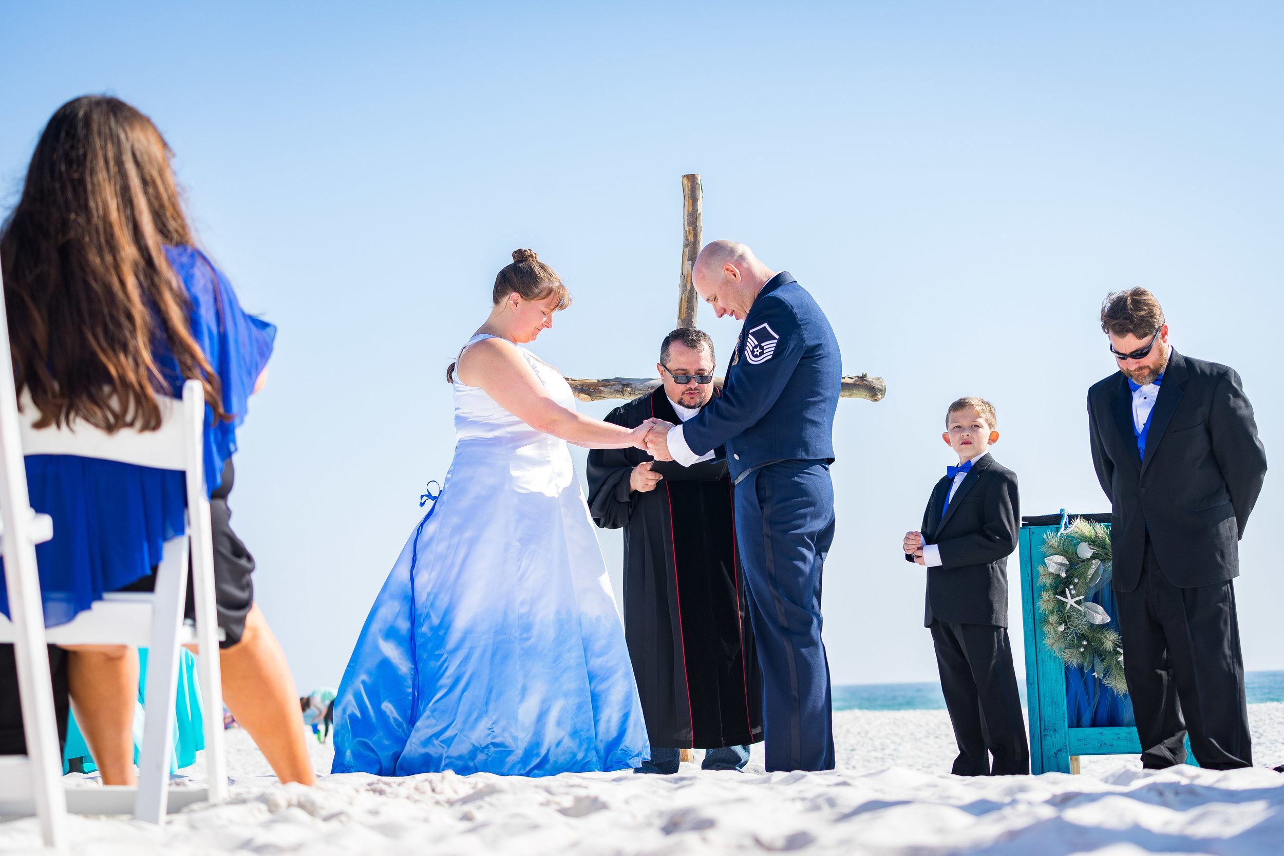image by photographer adam cotton of bride and groom praying during a pensacola beach florida wedding ceremony