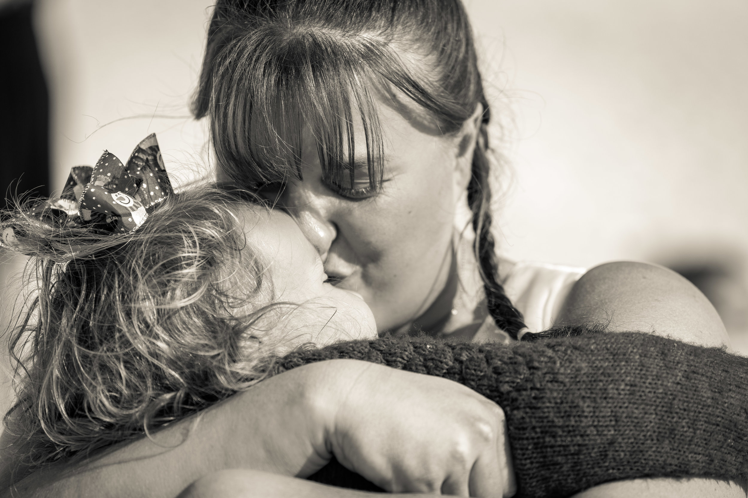 black and white close up image of bride and daughter hugging pensacola beach wedding by adam cotton