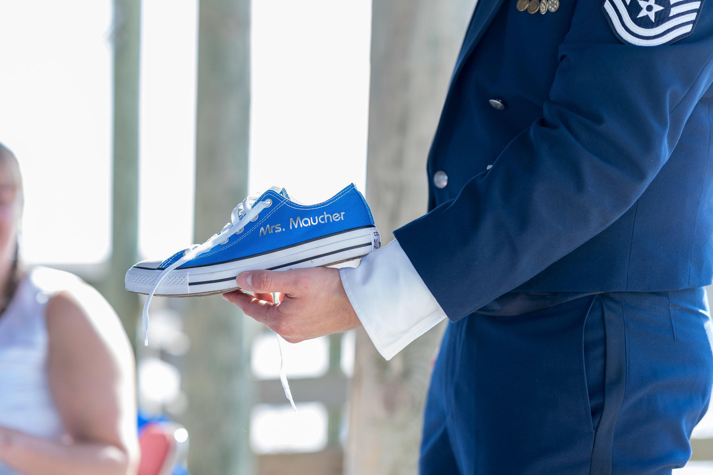 image of blue converse held by groom