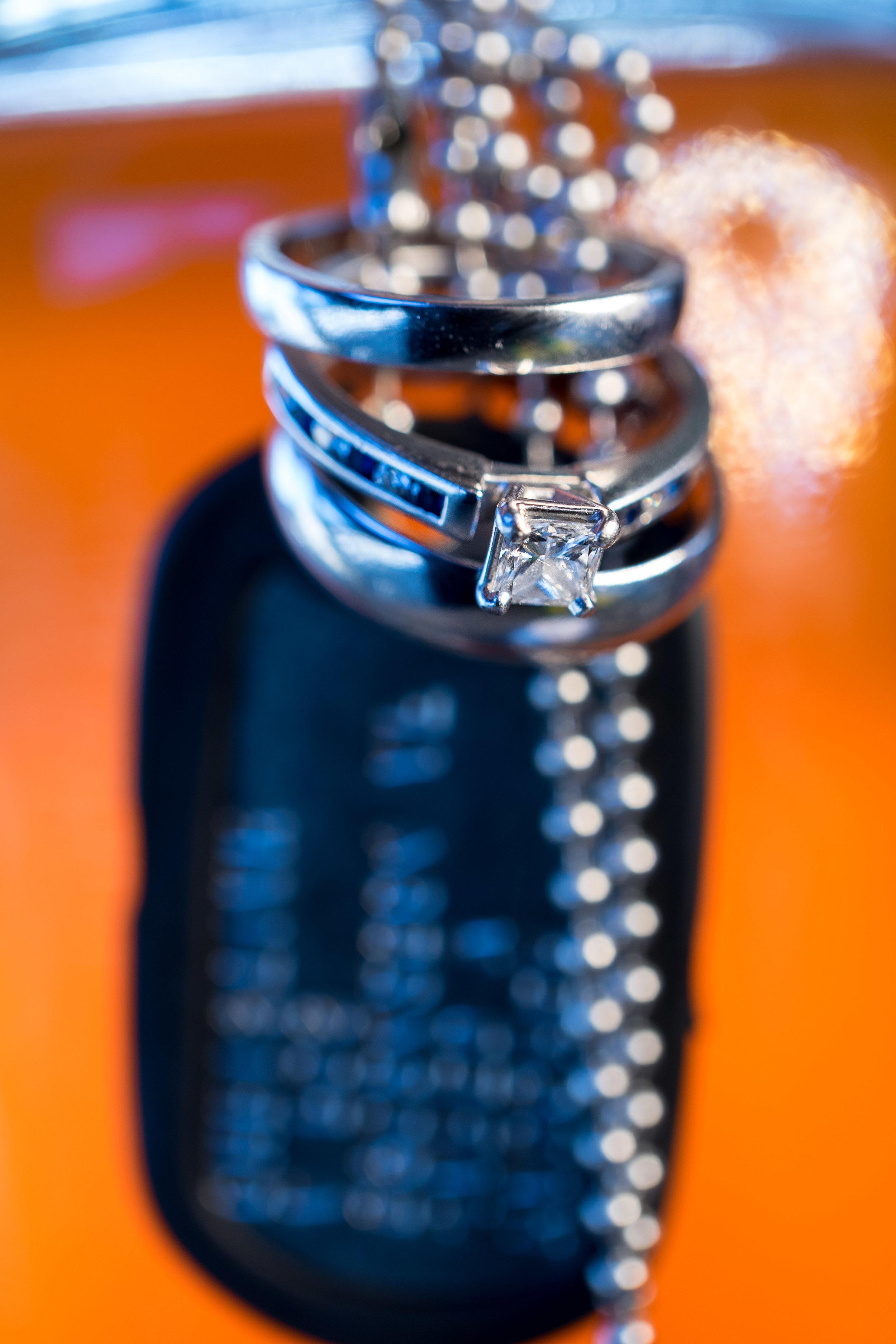 image of wedding rings dog tags and moonshine details pensacola florida wedding