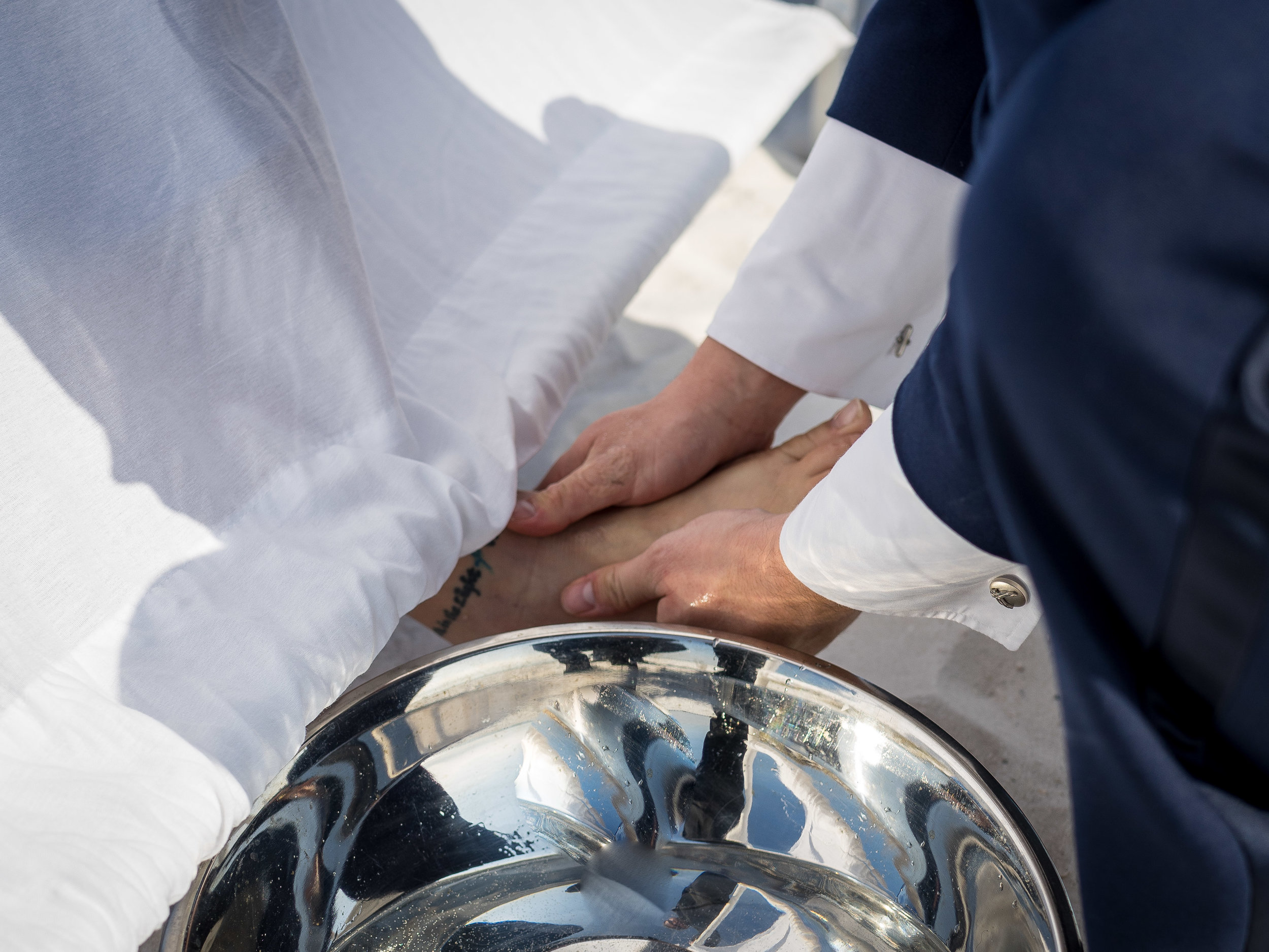 groom washing bride feet before wedding on pensacola beach