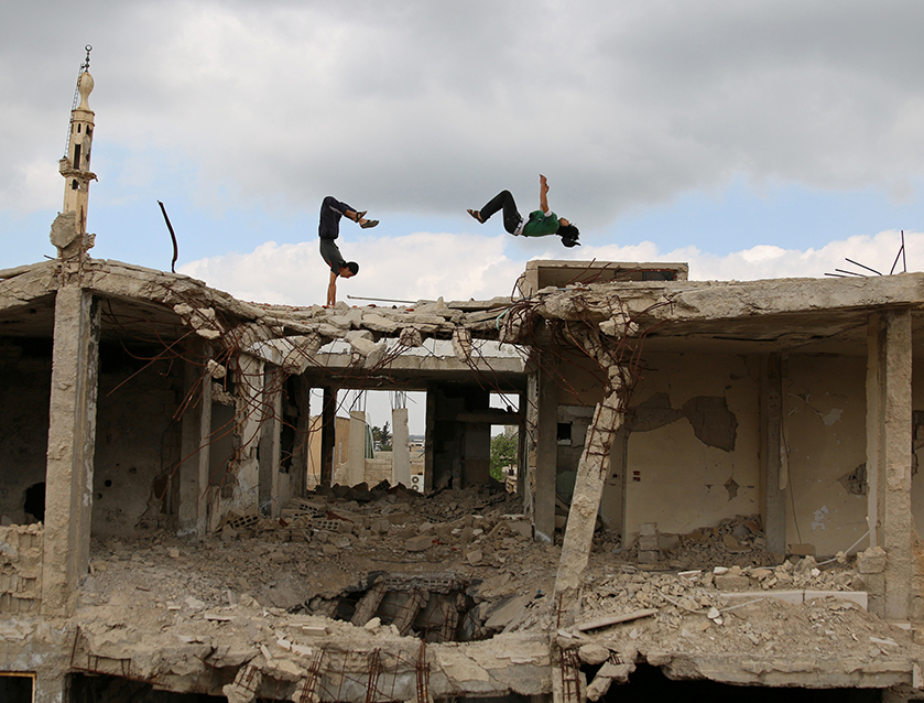 Ibrahim al-Kadiri and another parkour practitioner demonstrate their skills on damaged buildings in Inkhil, Syria.