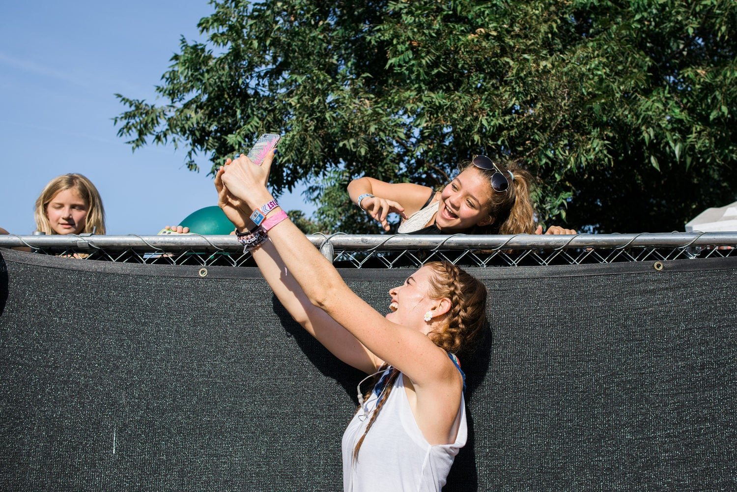Misterwives taking selfies over a fence