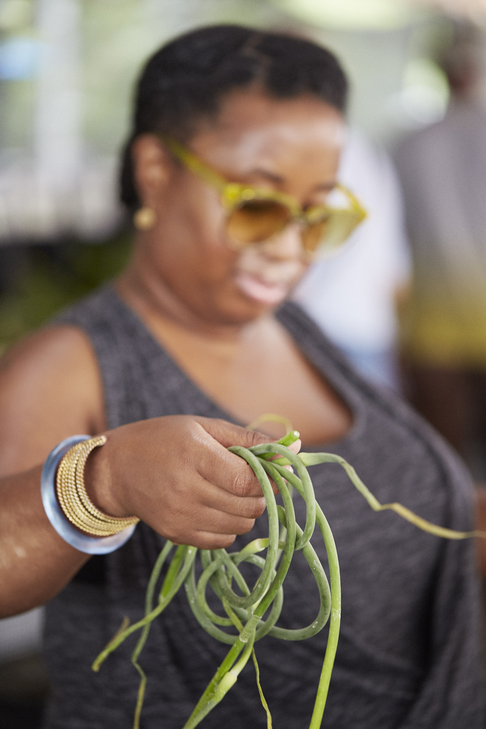 Nicole picking up some Garlic Scapes.