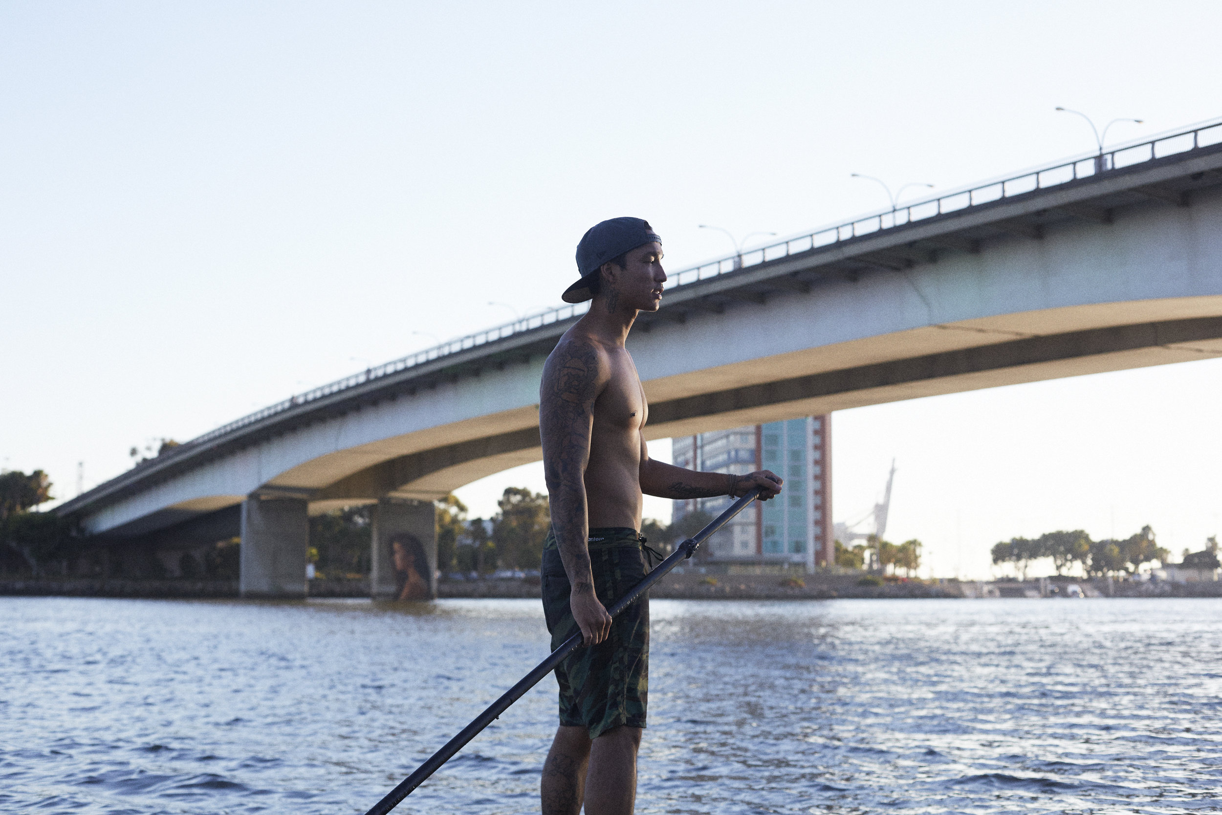 Sean Yoro on paddle board at dusk - his mural LUANA in the distance behind him.Long Beach, CA.