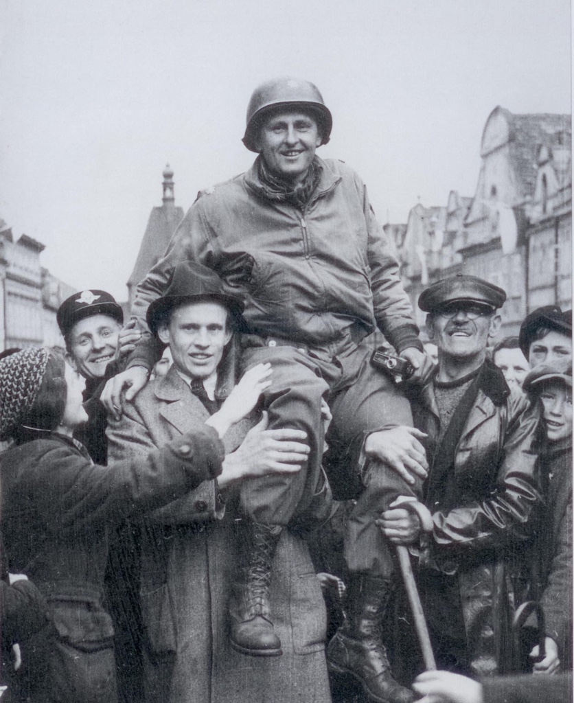 Matt Konop carried in the main square of Domazlice, Czechoslovakia on May 4, 1945. The photo was taken a few meters from Arnost Hruska's building. Note the movie camera in my grandfather's left hand.