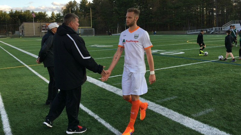 Creswick walks off the pitch at Lowell United FC with a handshake from Goalkeeping Coach Chuck Wilder.
