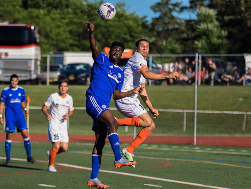 Stockade's Brandon Curtis goes up for a header against TSF FC. (Photo by Leanne Keator,  Ride the Tide Photography )