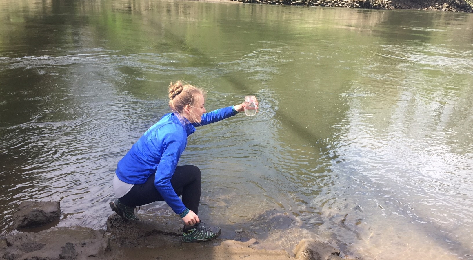 Corrine Armistead takes a water sample as part of a regional microplastics survey.