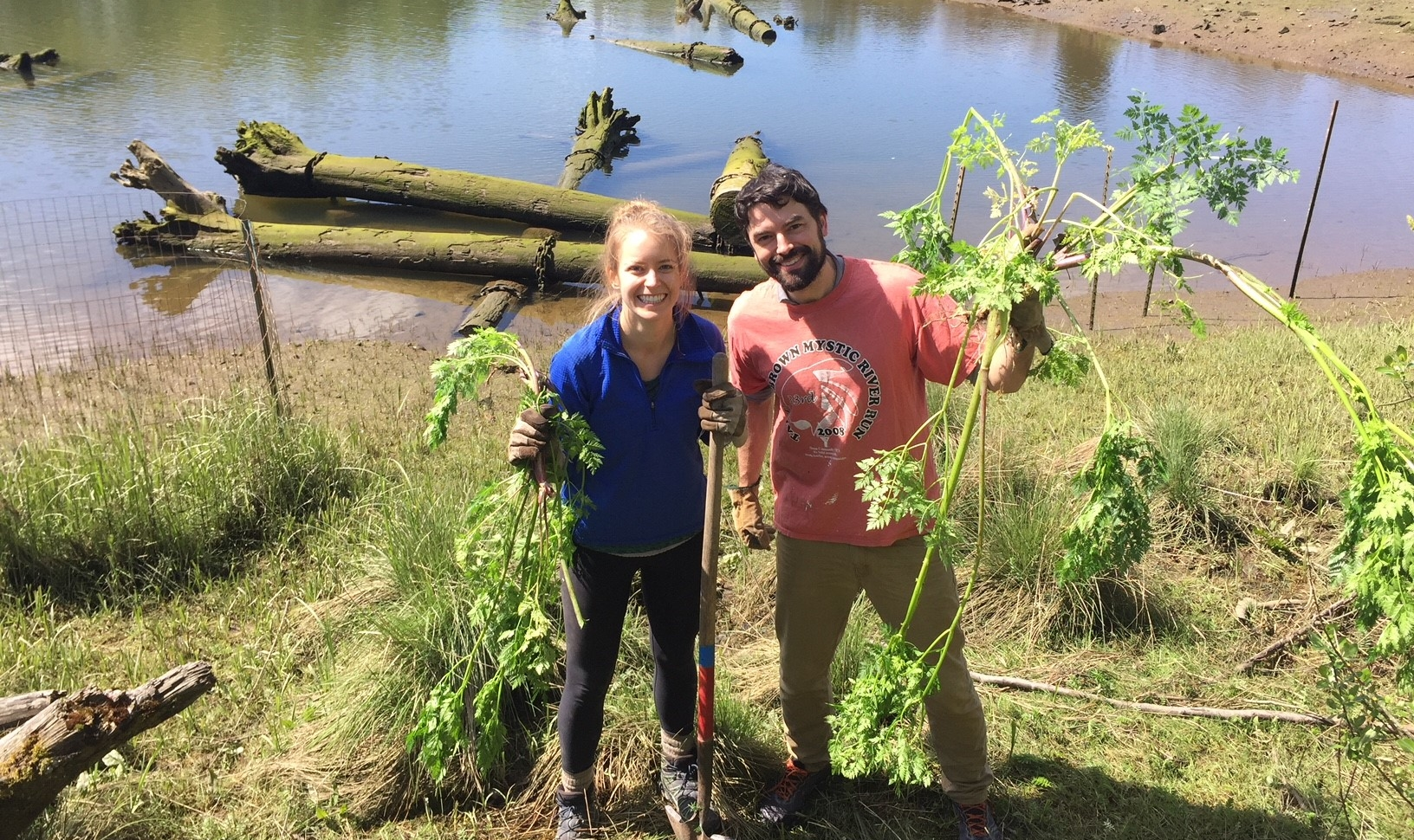 Corrine Armistead and Cyrus Philbrick holding poison-hemlock removed from North Winds Weir .