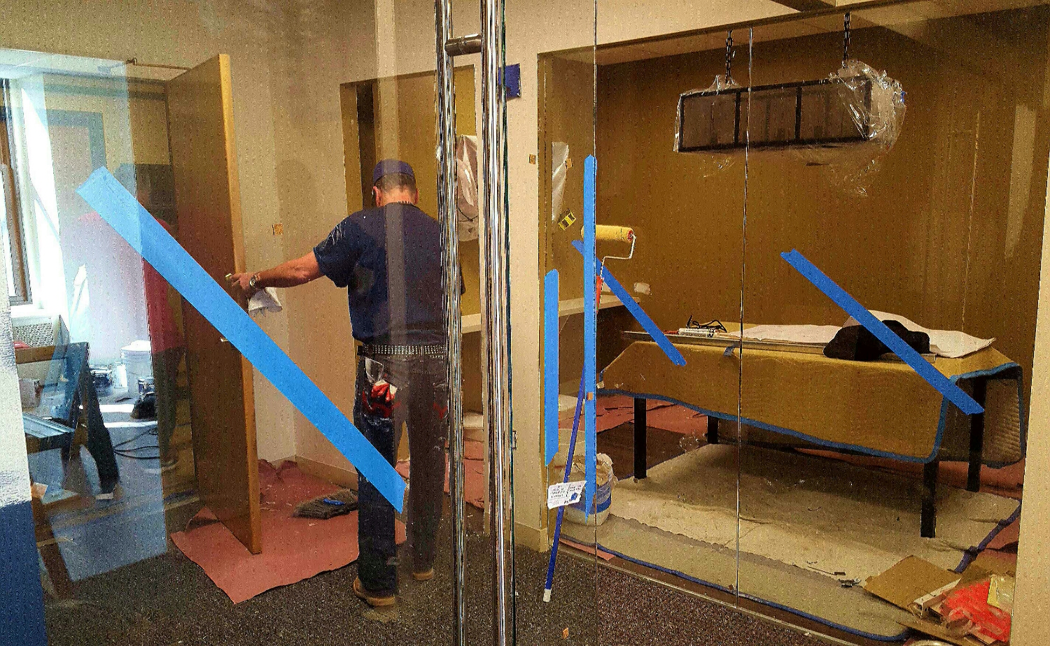 Progress is a good thing, contractors touching up the space. The glass is all installed.