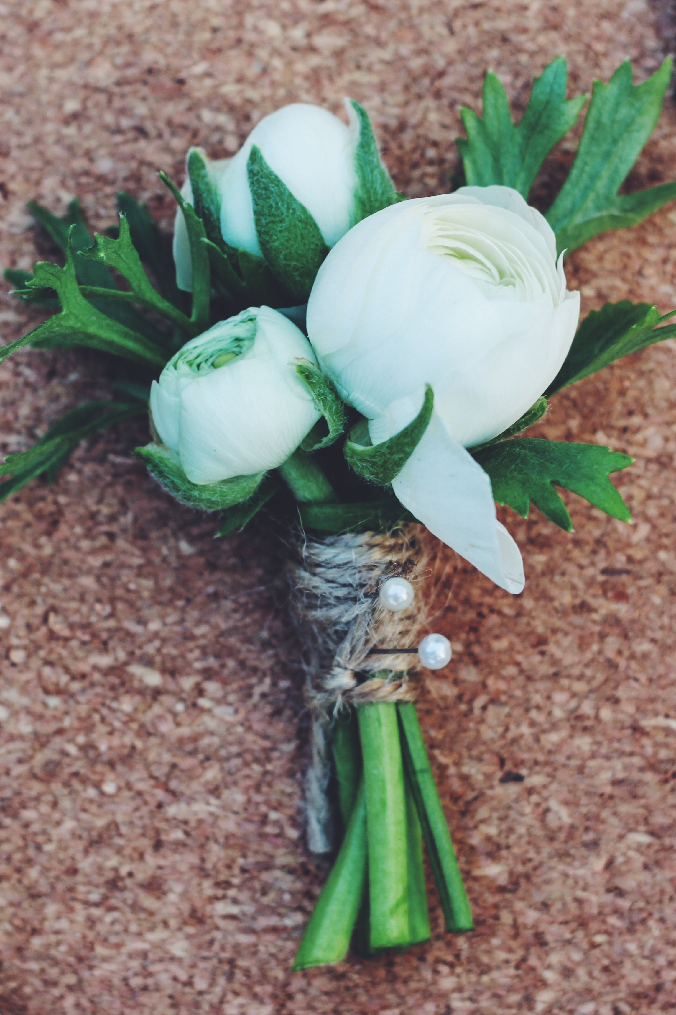 buttonholes by Jennifer Pinder tied with twine. White flowers with touches of peach. Flowers include ranunculus, spray roses and gypsophila.
