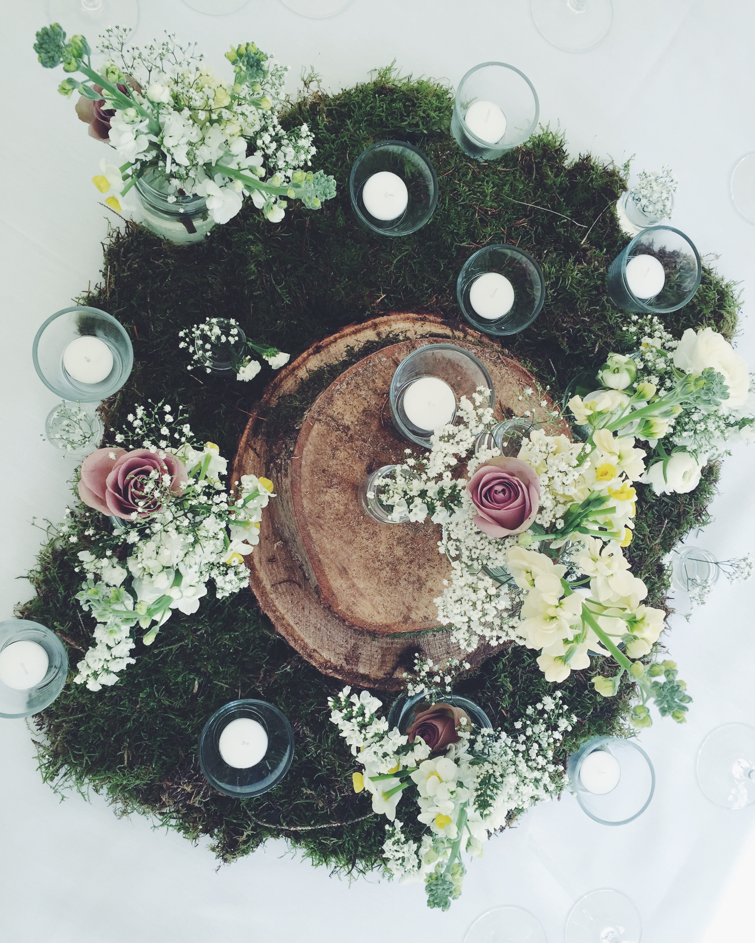 wedding table centrepiece by Jennifer Pinder at Fulham Palace in London. Includes moss, wooden slices and jam jar flowers with gypsophila, stock, roses, ranunculus and narcissi