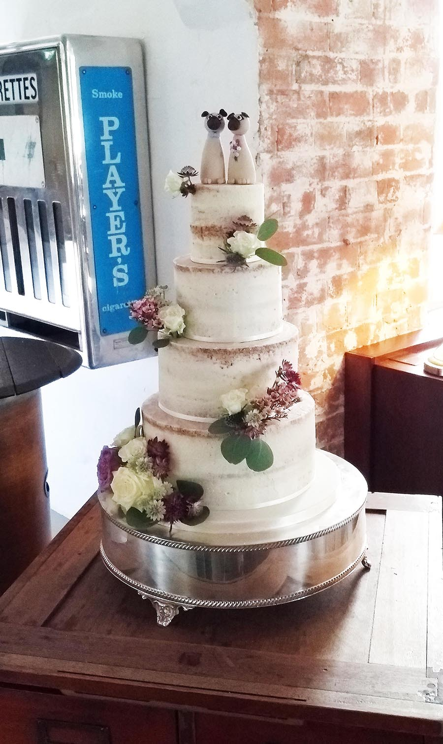 Semi-naked wedding cake with commissioned pug dog toppers