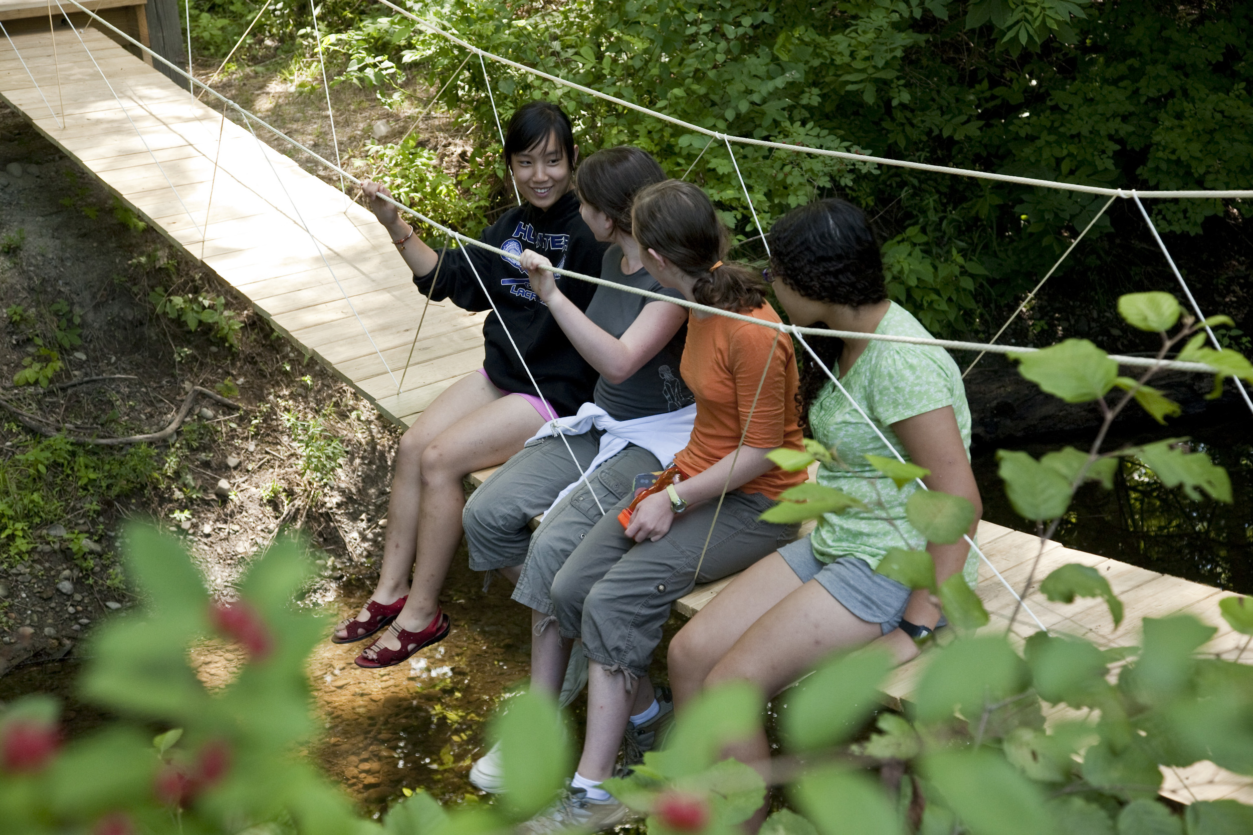 A camper built a suspension bridge that spans a small creek behind the pond.