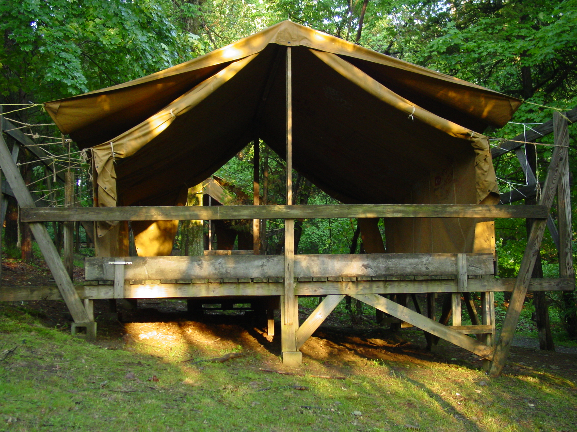 Campers sleep on cots in wooden-platform canvas tents like these.