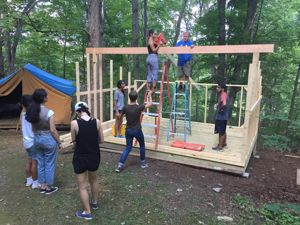 Campers building the lean-to during projects time. This will be used for sleeping space.