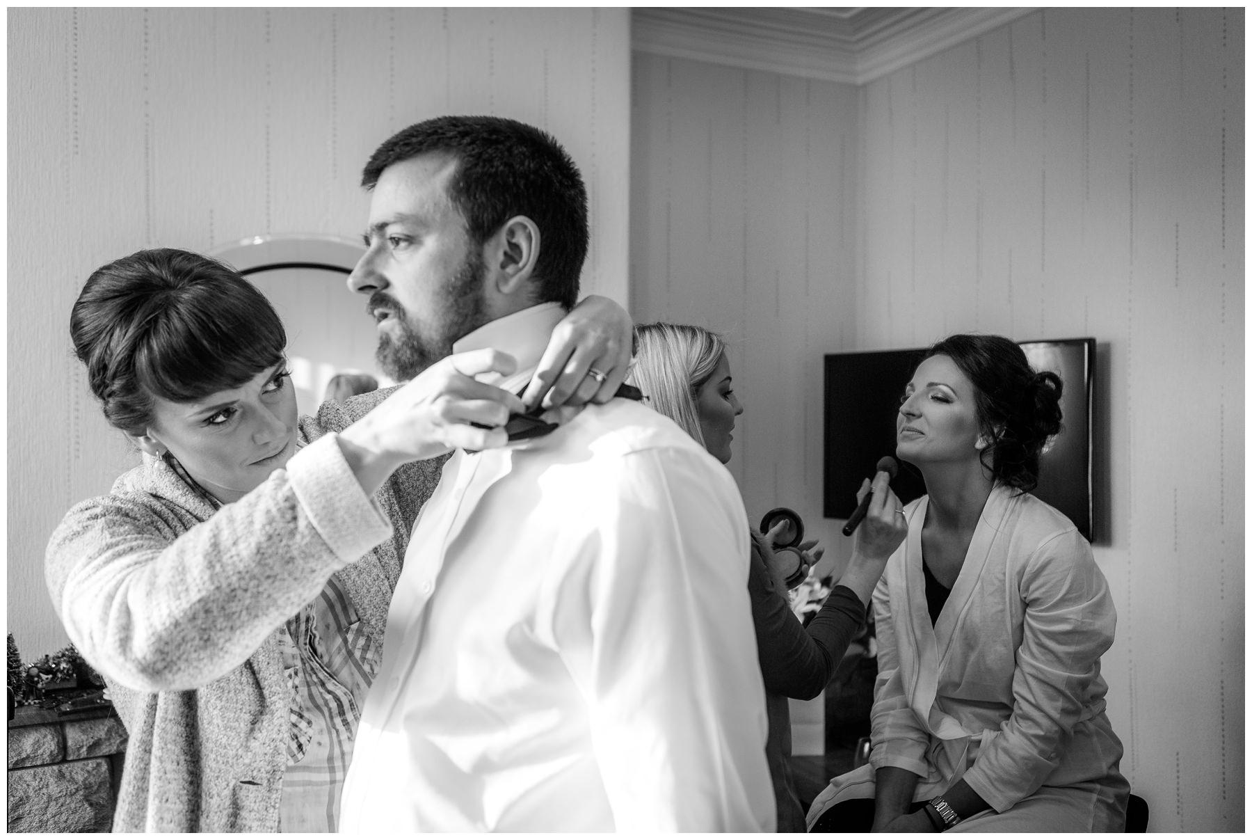 bridesmaid helping brides brother with his tie