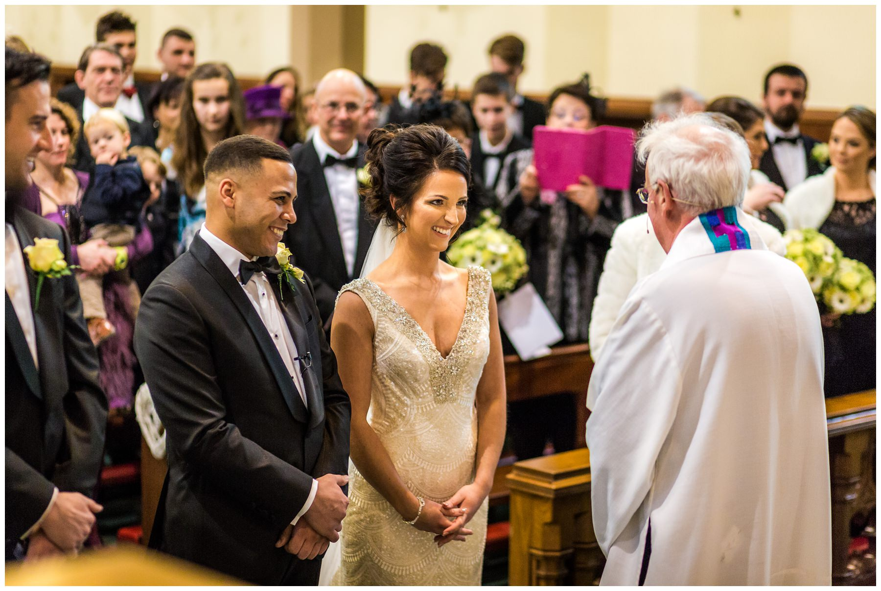 bride smiling at the end of the aisle stood next to groom