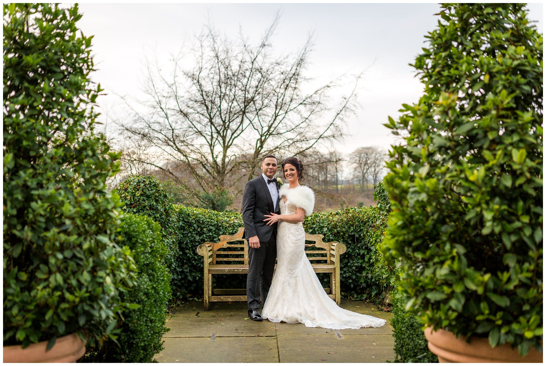bride and groom portrait between trees in gardens of mitton hall, north west wedding photographer