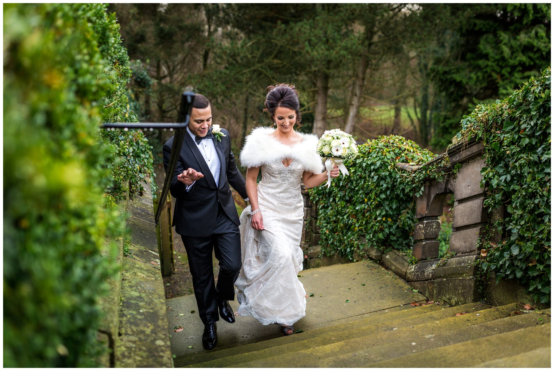 bride and groom naturally walking up the stairs in gardens of mitton hall, north west wedding photography