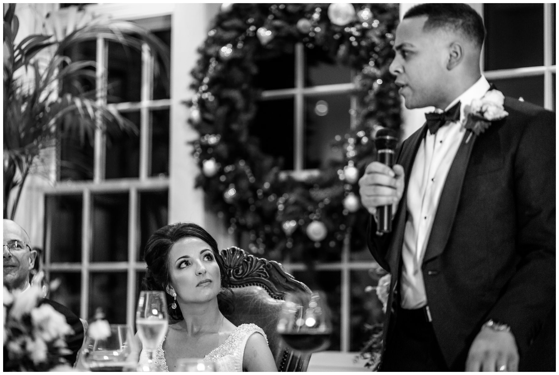 groom giving his wedding speech while bride watches