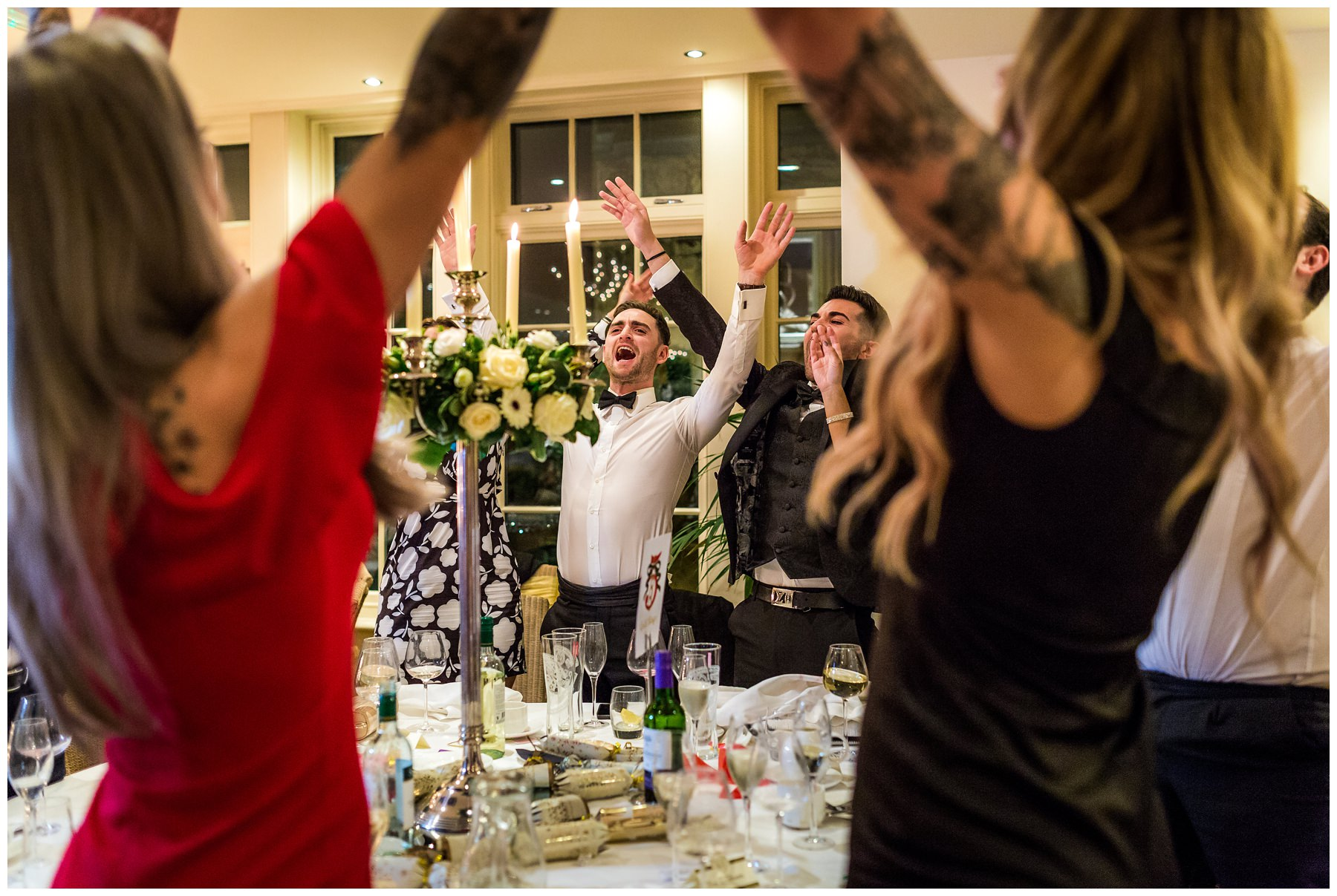 shot of guest singing christmas carols after wedding breakfast