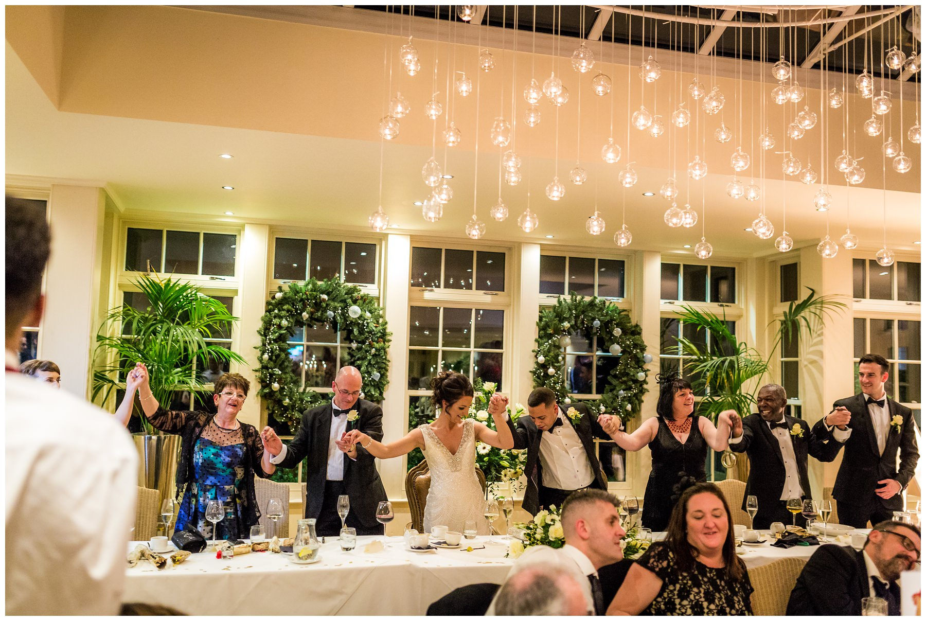 wide shot of the top table singing and swaying