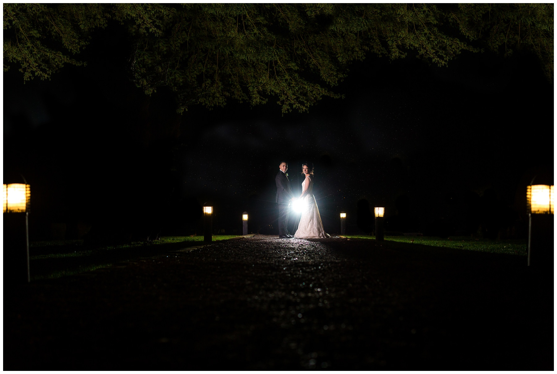 bride and groom stood in the dark outside with a path of lights leading up to them