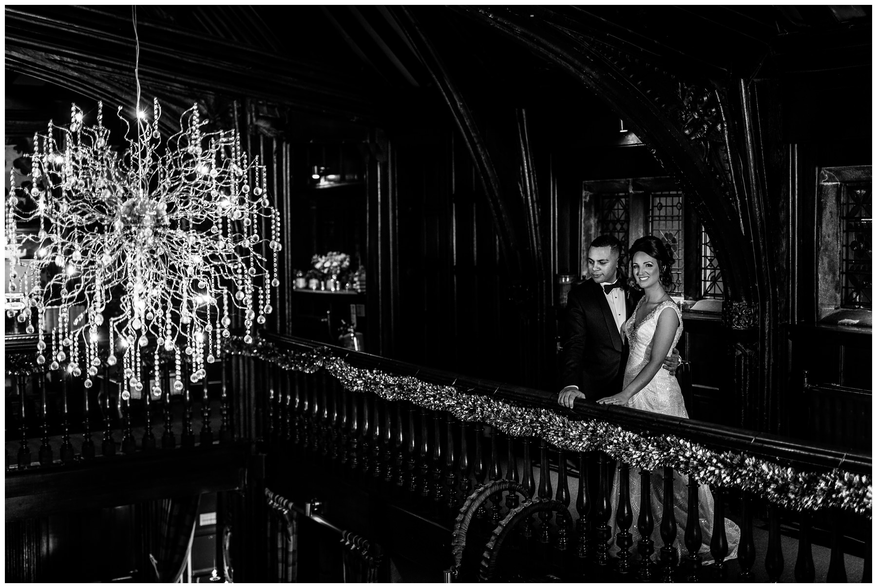 bride and groom stood by chandelier in Mitton Hall, North West