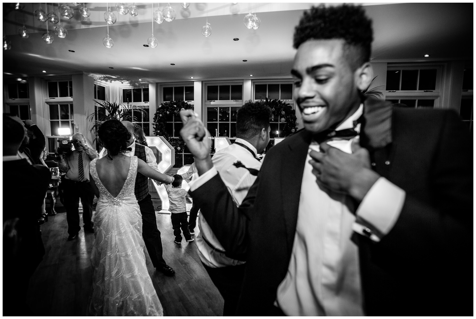 grooms brother dancing while bride and groom dance together in the background