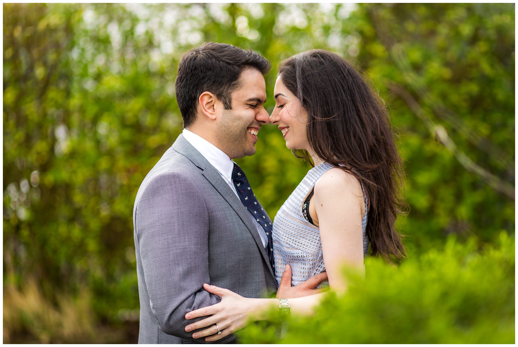couple face to face with green plant backdrop