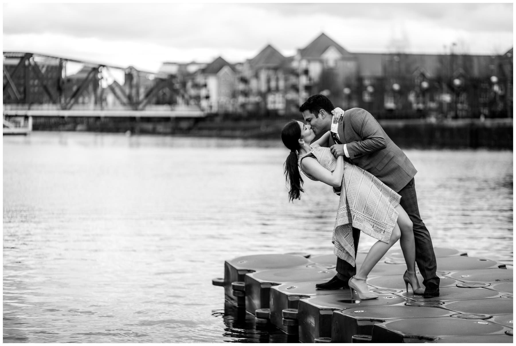 groom dipping his bride over water