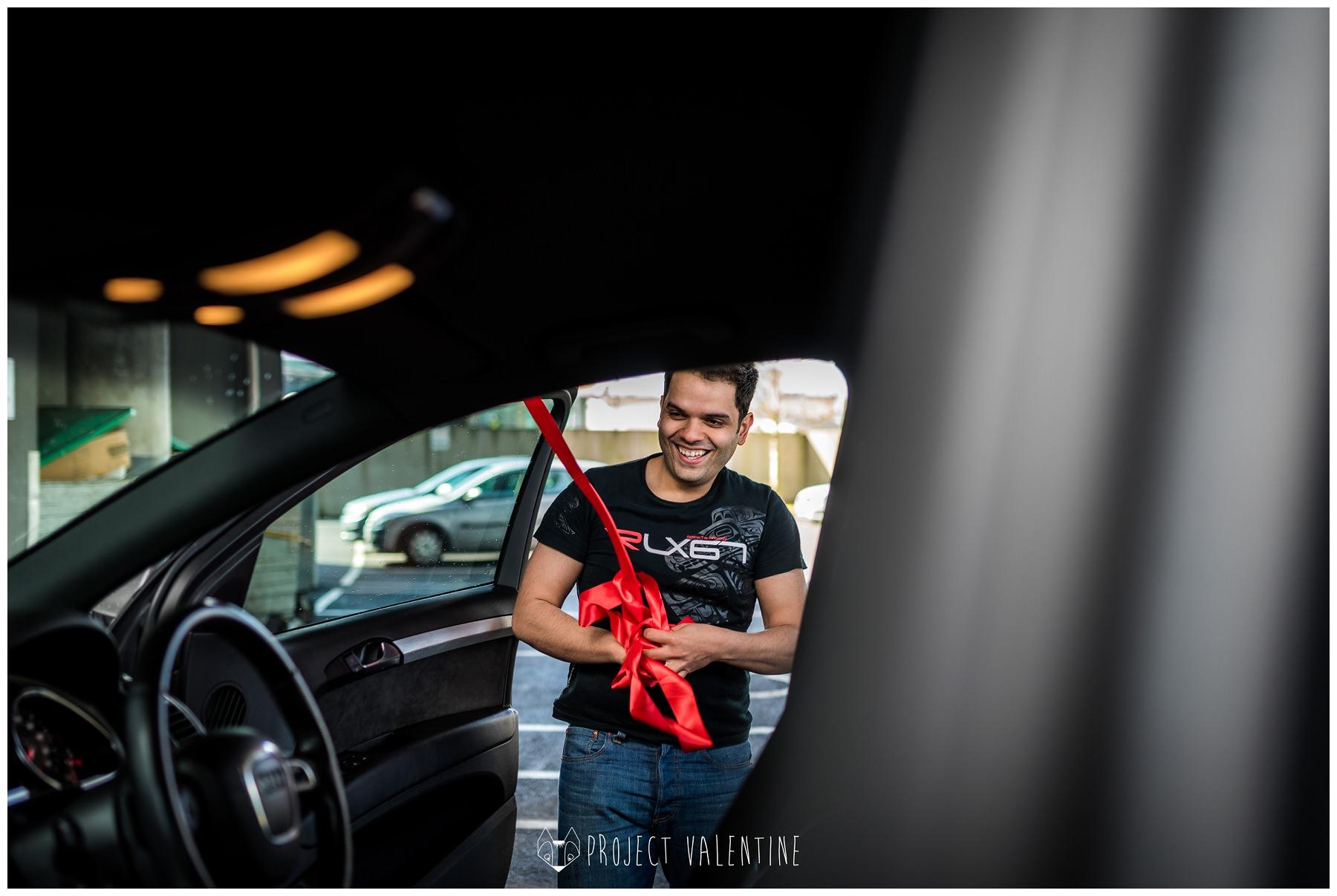 groom putting ribbon onto wedding car