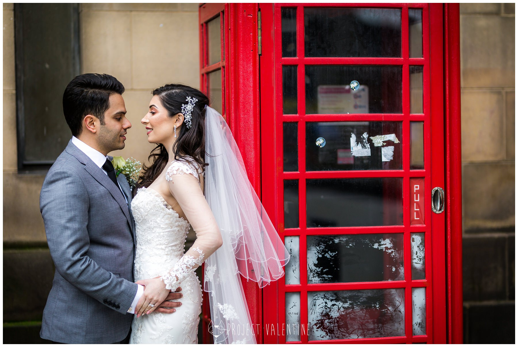 bride and groom cuddling by red phone box