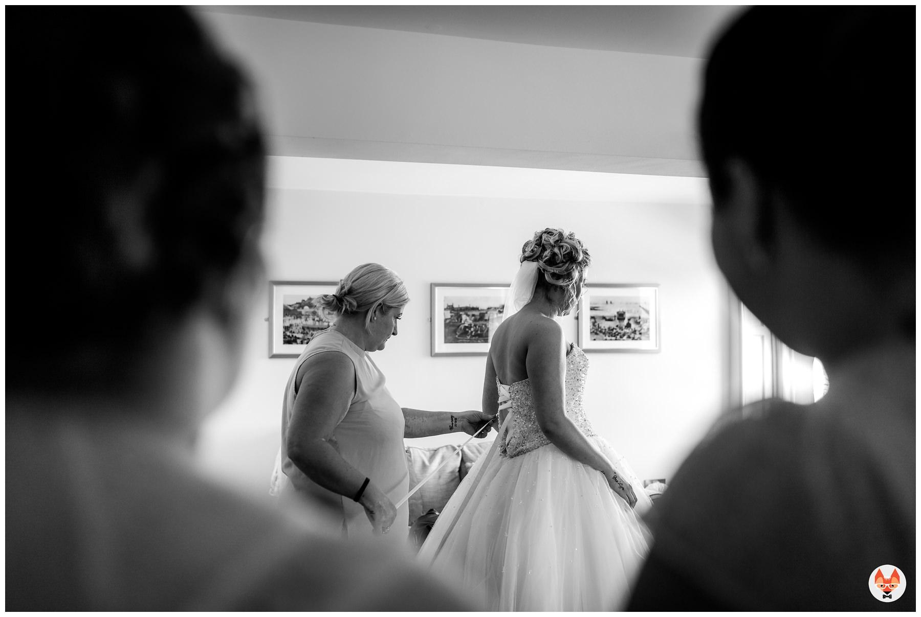 bride having her dress fastened up