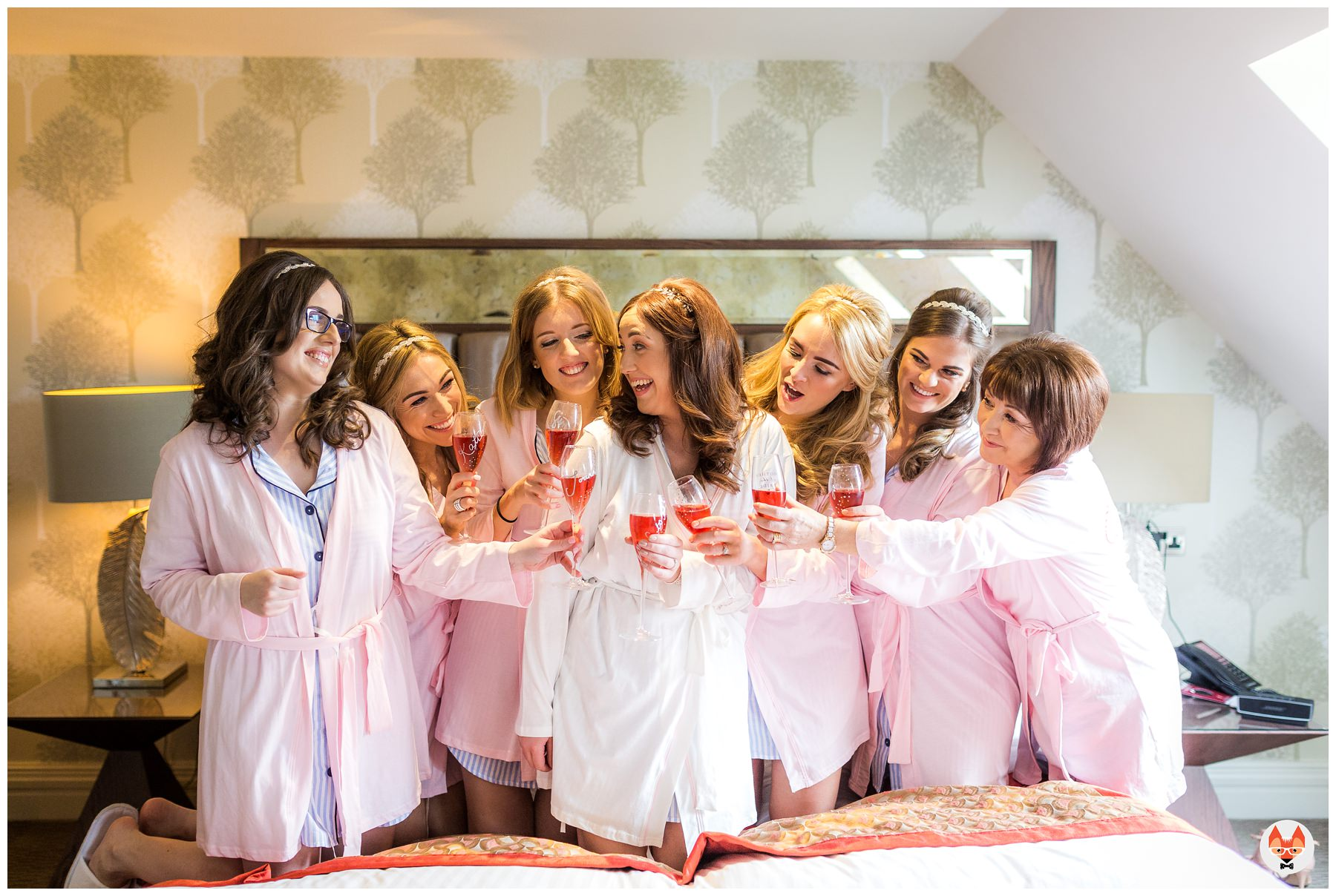 bride sat with bridesmaids on bed