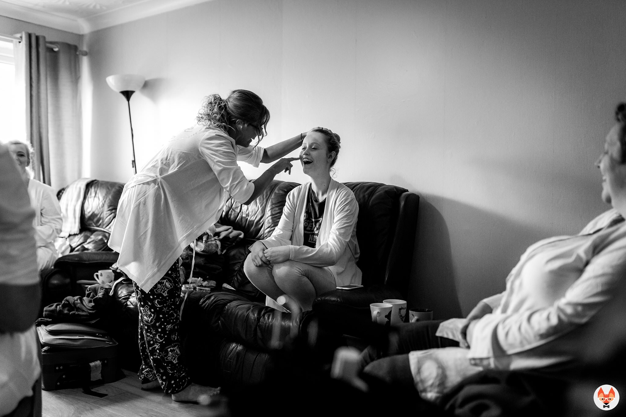 bride helping sister with makeup
