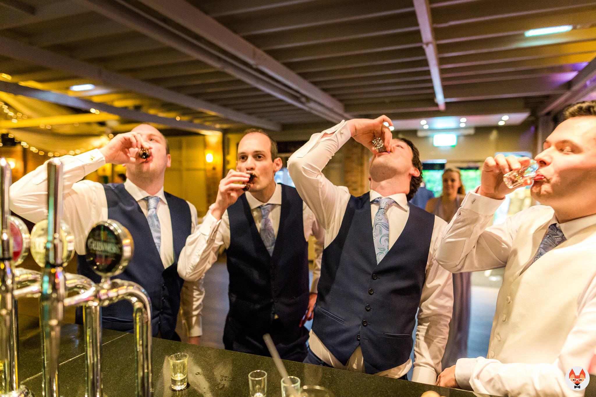 groomsmen doing shots at bar
