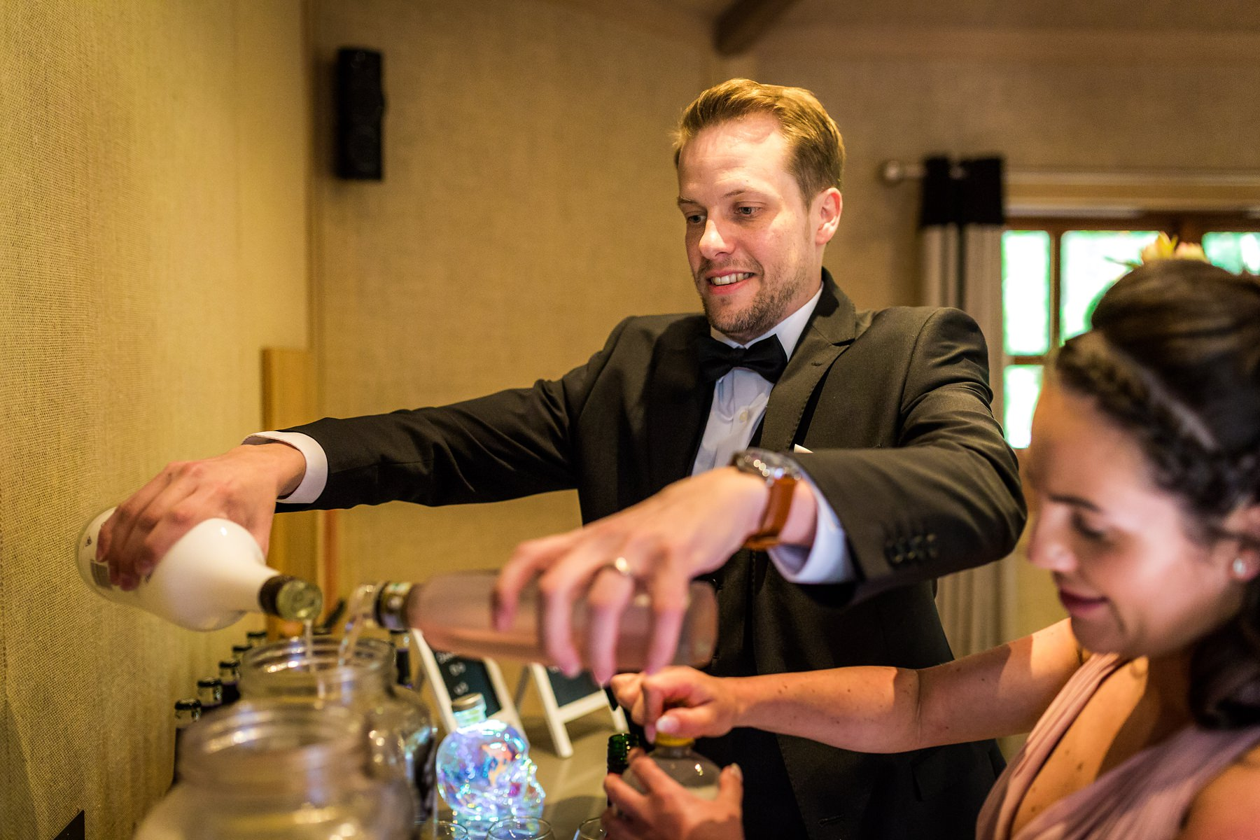 groom making his own cocktails