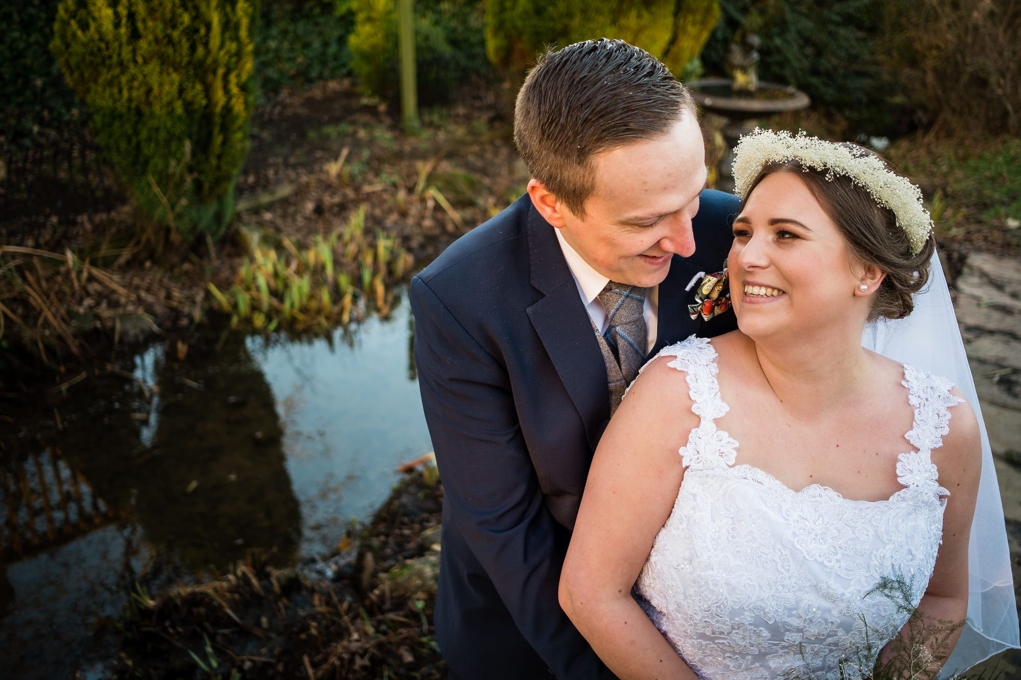 bride and groom by pond at stirk house