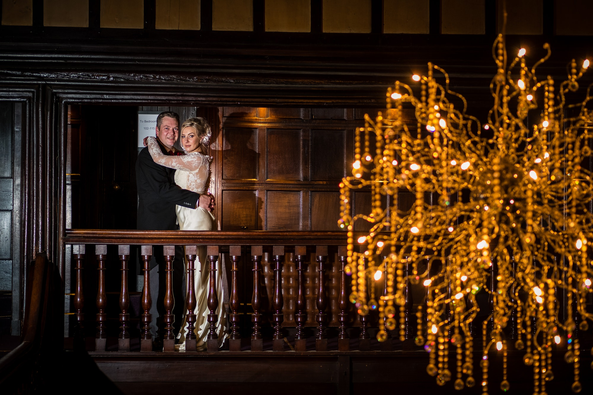bride and groom in front of chandelier