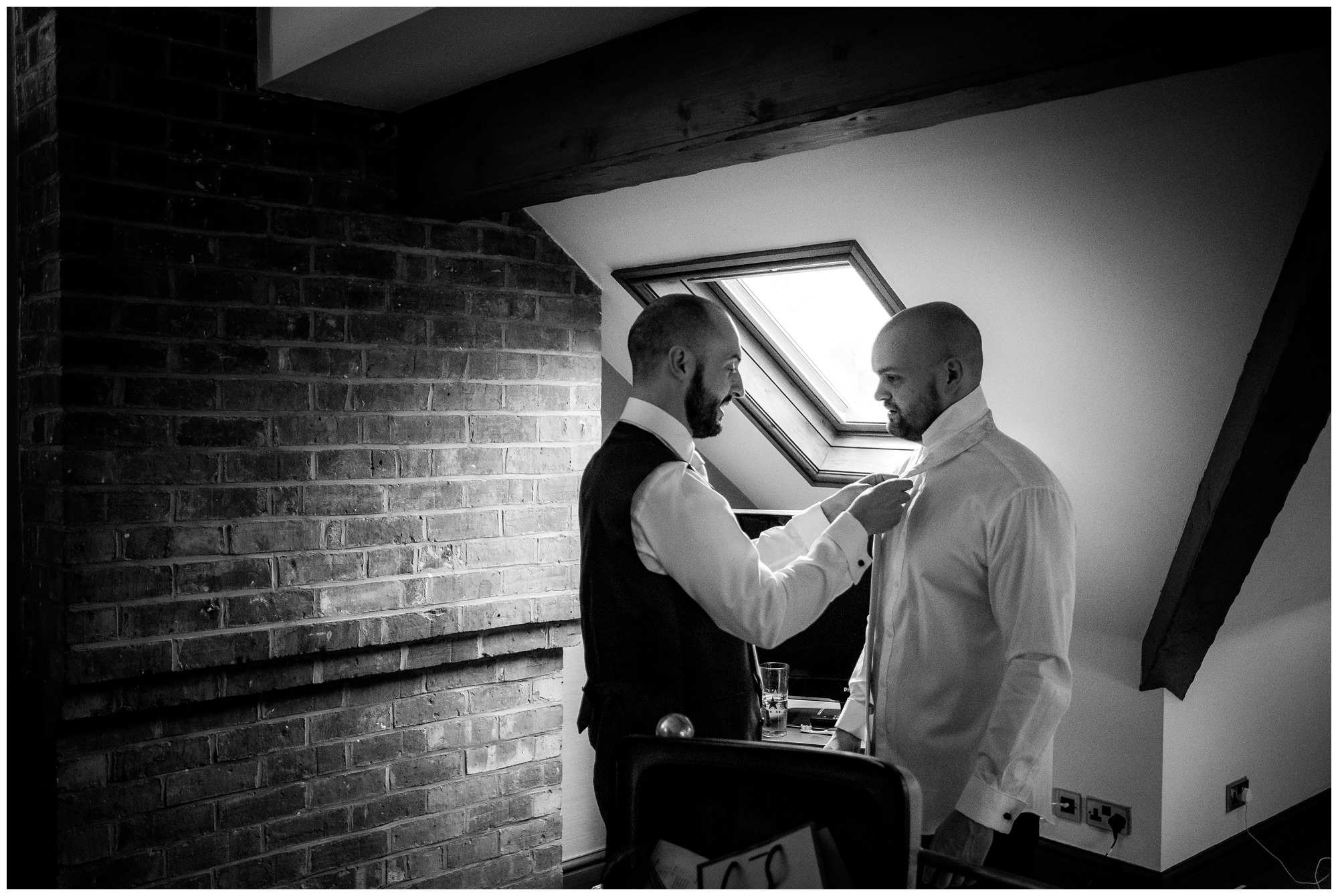 usher putting on grooms tie