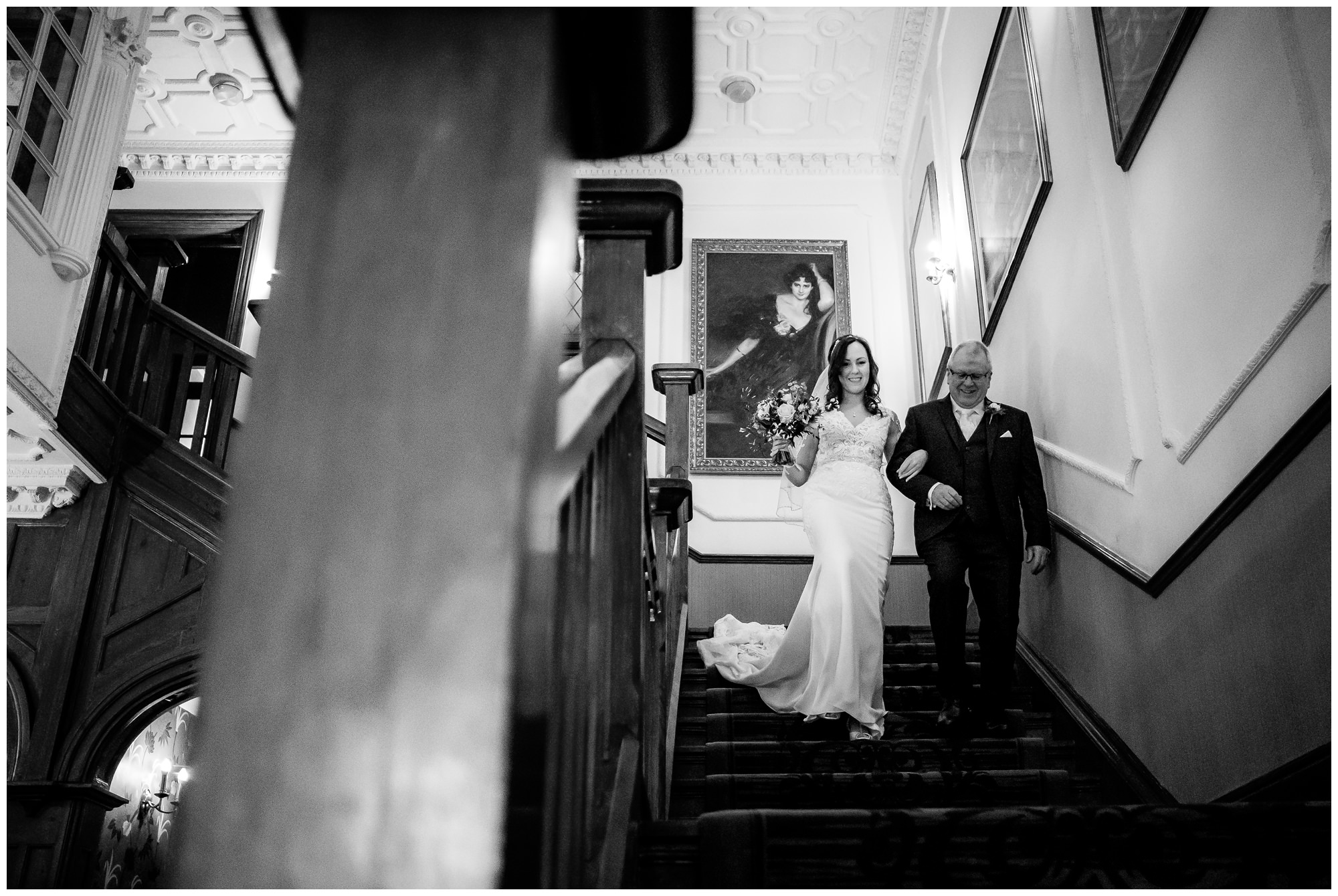 dad walking bride down staircase at nunsmere hall, cheshire
