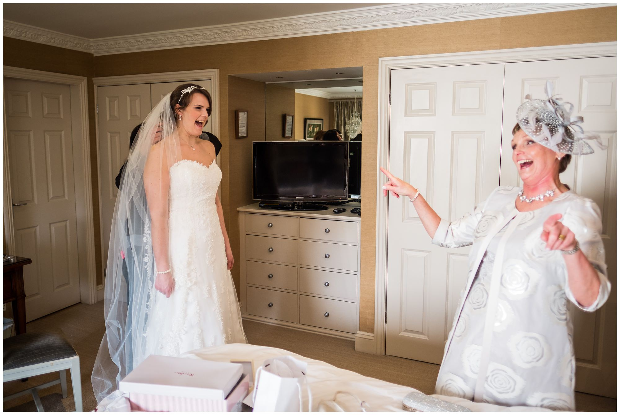 bride and her mum laughing while in dress